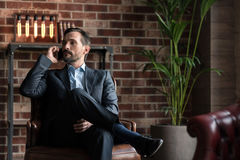 Serious successful businessman having a conversation. Involved in the discussion. Good looking attractive confident man sitting in an armchair and listening Stock Photography