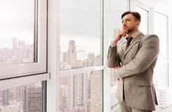 Serious successful businessman standing in the office Royalty Free Stock Photo