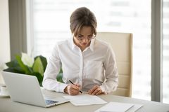 Serious successful businesswoman puts signature on business cont. Ract, millennial female entrepreneur signing paper doing paperwork at workplace, woman boss stock photos