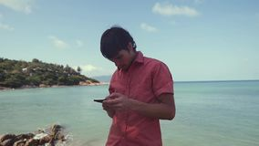 Serious successful man uses smart phone sitting near the tropical beach. slow motion. 1920x1080. Hd stock footage