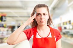 Supermarket employee touching temple as salute gesture royalty free stock image