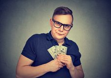Serious suspicious greedy man with money. Serious suspicious greedy young man in glasses with money dollar banknotes Stock Image