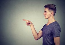 Serious suspicious young man pointing finger at someone. Serious suspicious man pointing finger at someone frowning isolated on gray background Stock Photos