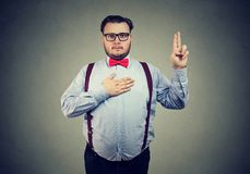 Serious taking oath and gesturing. Confident serious man in formal outfit holding hand on chest and making promise looking at camera royalty free stock photos