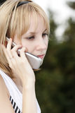 Serious talk. Pretty girl listening mobile phone with serious expression Stock Photography
