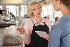 Concentrated waitress discussing menu with her employer. Serious talk. Serious blond waitress holding a tablet and talking with her young employer stock photography