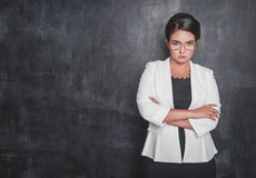 Serious teacher looking at you on blackboard. Background stock photo