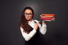 Serious teacher pointing at pile of textbooks Royalty Free Stock Photos