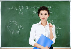 Serious teacher stands at the blackboard Royalty Free Stock Image