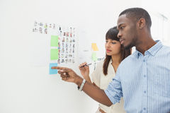 Serious teamwork pointing sticky notes together Royalty Free Stock Photos