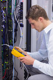 Serious technician using digital cable analyzer on server Royalty Free Stock Images