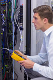 Serious technician using digital cable analyzer on server Stock Image