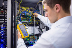 Serious technician using digital cable analyzer on server Stock Photo