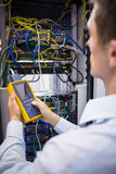 Serious technician using digital cable analyzer on server. In large data center Stock Image