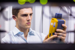 Serious technician using digital cable analyzer on server Stock Photography