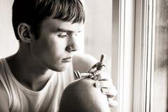 Serious teen boy looking at wooden manikin Royalty Free Stock Photo