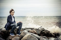 Serious Teen Boy Sitting on Rocks at the Seaside Stock Image