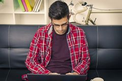 Serious teen boy typing on laptop. Serious teenage boy sitting on a couch using a laptop, looking down toward the keys with a serious expression Royalty Free Stock Image