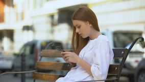 Serious teen girl scrolling on smartphone during bench rest, gadget addiction. Stock footage stock video footage