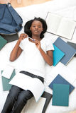 Serious teen girl studying lying on her bed Stock Photography