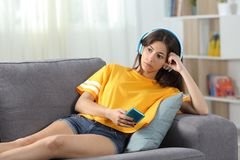 Serious teen listening to music online at home. Serious teen listening to music online looking away sitting on a couch in the living room at home Stock Photo
