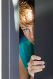 Serious teen peeking from between door and wall stock photos
