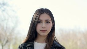 Portrait of a beautiful ethnic girl looking at camera closeup. Serious teenage Asian mixed-race brunette girl outdoor. Portrait of a beautiful ethnic girl stock video footage