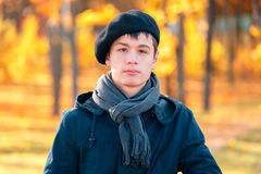 Serious teenage boy in the autumn sunny park Stock Photography