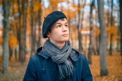 Serious teenage boy in the autumn sunny park Royalty Free Stock Image