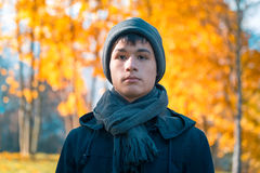 Serious teenage boy in the autumn sunny park Royalty Free Stock Photos