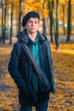 Serious teenage boy in the autumn sunny park Royalty Free Stock Photo