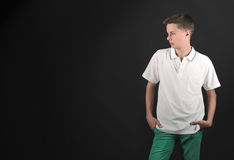 Serious teenage boy looking away. On black background Stock Photography