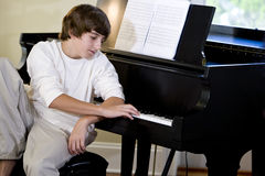 Serious teenage boy looking down at piano keys Royalty Free Stock Images