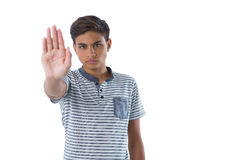 Serious teenage boy showing stop sign. Portrait of serious teenage boy showing stop sign Royalty Free Stock Photos