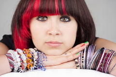 Serious teenage girl. Closeup of a serious teenage girl leaning on her arms, wearing multiple colorful bracelets and pink/red highlights in her hair Royalty Free Stock Photography