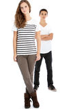 Serious teenage girl posing with her brother. Serious teenage girl in trendy modern clothing posing full body with her brother with the girl in the foreground Stock Photography