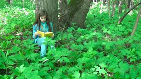 Portrait of serious teenage girl reading book and turning page leaning against tree trunk in forest in spring, studying. Serious teenage girl reading book and stock video