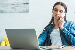 serious teenage girl talking by smartphone and using laptop stock photo