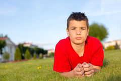 Serious teenage summer lies in the grass Stock Photo