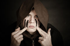 Serious teenaged boy smears paint on his face. With fingertips while wearing dark hooded garment Royalty Free Stock Images