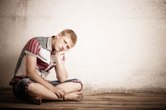 Serious teenager boy. Sitting on old wooden floor Royalty Free Stock Photos