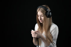 A serious teenager girl in listening music in wired headphones Stock Images