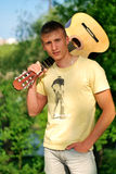 Serious teenager holding a guitar. In the park stock photos