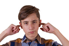 Serious teenager in plaid shirt holding fingers in ears Stock Image