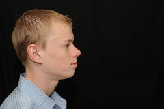 Serious teenager profile. Portrait of a serious teenage boy on black background Stock Photo