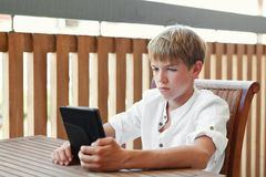Serious teenager reading e-book. Indoor Royalty Free Stock Image