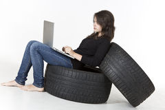 Serious teenager working on computer. Serious young girl is sitting on tires working on laptop isolated on white Stock Photos