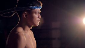A serious Thai Boxing fighter wearing a mongkol. A side view on a walking fighter wearing a blue braided headband stock video footage
