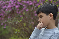 Serious Thinker. Little boy looking down with hand to chin in deep thought. He may be thinking about the future or concerned about the Earth Stock Image