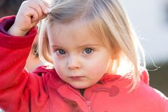 Serious thinking or sad young baby caucasian blonde real people girl close portrait outdoor.  Stock Photo